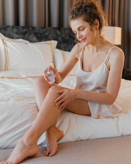 Kobieta w piżamie w domu stosując balsam na ciele
