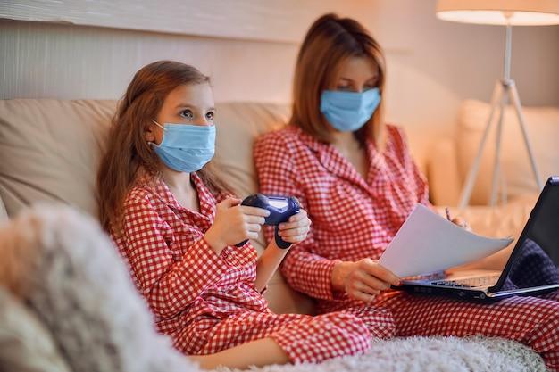 Kobieta w piżamie z notatnikiem i papierami pracującymi w domu, nosząca maskę ochronną, podczas gdy jej córka gra w gry komputerowe