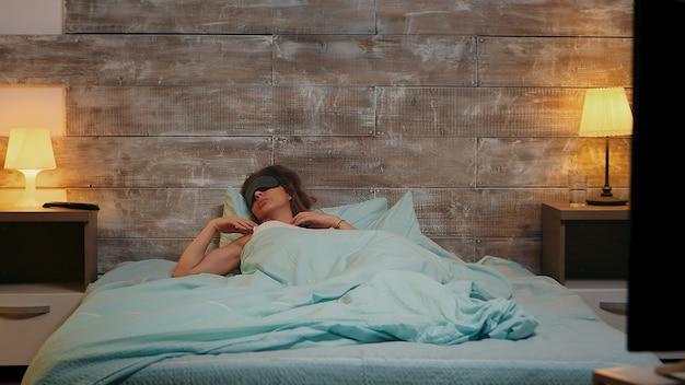 Kobieta w piżamie źle śpi z maską na oczy, gdy telewizor jest włączony.