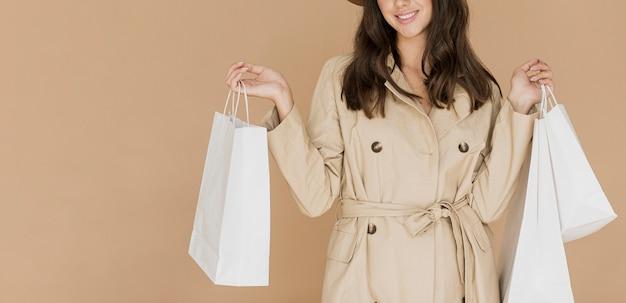 Kobieta w płaszczu beżowym z wieloma torbami na zakupy