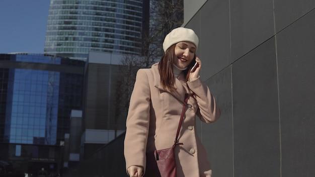 Kobieta w płaszczu idzie do centrum miasta, rozmawiając przez telefon.