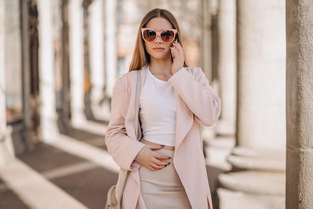 Kobieta w płaszczu spaceru na ulicy i rozmawia przez telefon