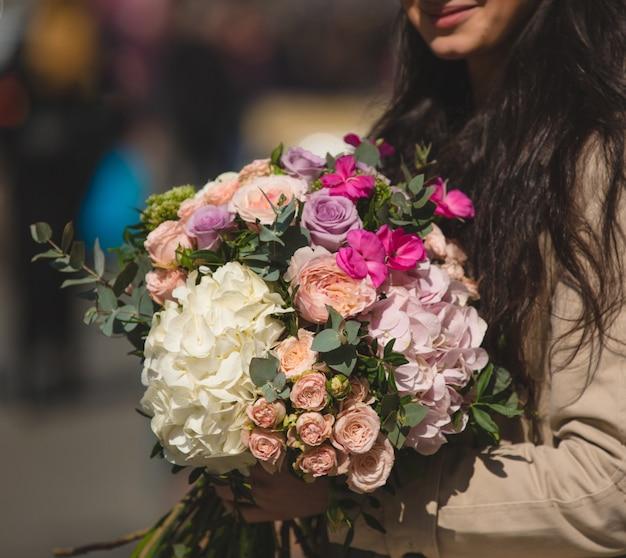 Kobieta w płaszczu trzyma mieszany bukiet kwiatów zimowych.