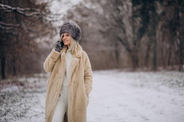 Kobieta w płaszczu zimowym spacerująca w parku pełnym śniegu rozmawiająca przez telefon