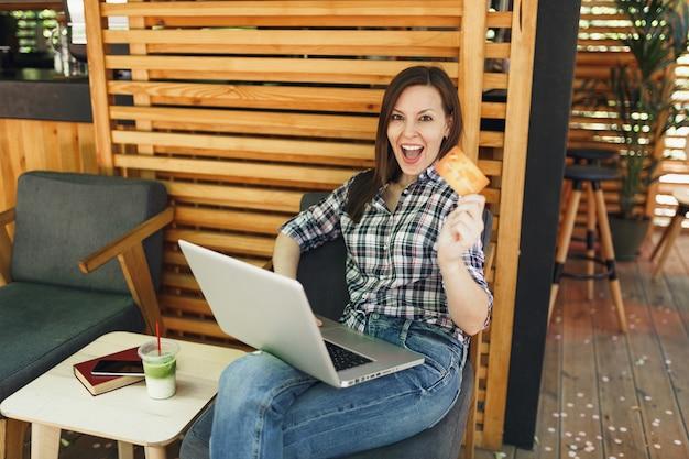 Kobieta w plenerze ulica letnia kawiarnia drewniana kawiarnia siedząca pracująca na komputerze przenośnym, trzymaj kartę kredytową banku relaksując się w czasie wolnym