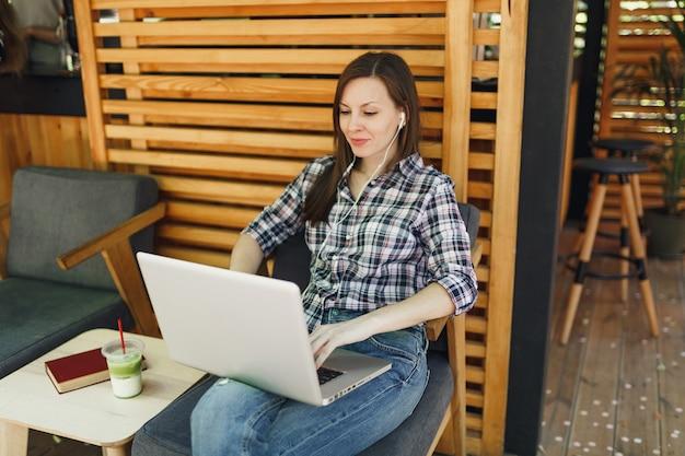 Kobieta w plenerze ulica letnia kawiarnia drewniana kawiarnia siedząca w codziennych ubraniach, pracująca na nowoczesnym komputerze typu laptop pc pc