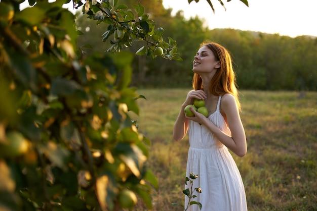 Kobieta w pobliżu drzew z jabłkami w ręce na charakter latem