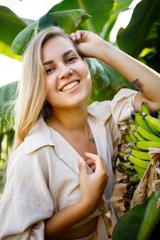 Kobieta w pobliżu dużego zielonego liścia drzewa bananowego na przyrodę w parku. rośliny tropikalne