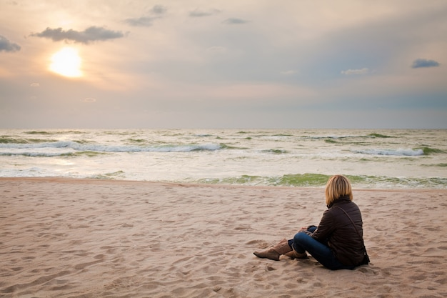 Kobieta w pobliżu morza o zachodzie słońca