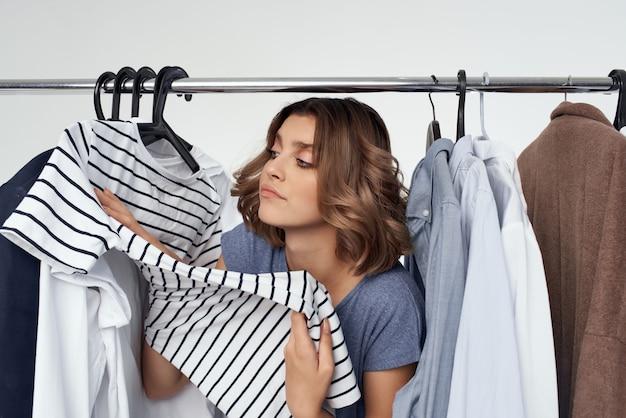 Kobieta w pobliżu ubrania zakupoholiczka na białym tle. zdjęcie wysokiej jakości