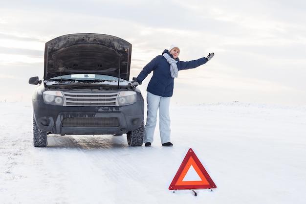 Kobieta w pobliżu zepsutego samochodu. ona prosi o pomoc. wokół zimy i śniegu. jest znak awaryjny.