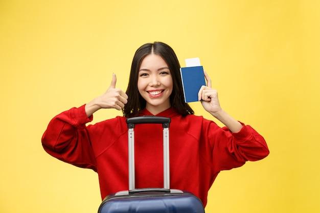Kobieta w podróży. młoda piękna azjatycka kobieta podróżnik z paszportem i walizką