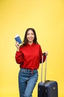 Kobieta w podróży. młody piękny azjatycki podróżnik kobieta z walizką i paszportem