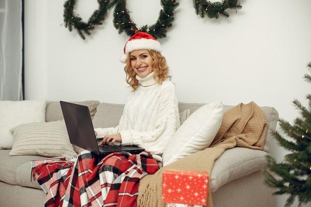 Kobieta w pokoju. blondynka w białym swetrze. pani z laptopem.