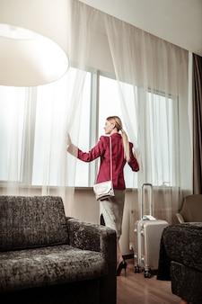 Kobieta w pokoju. stylowa blond-włosa bizneswoman studiuje swój pokój hotelowy podczas podróży służbowej