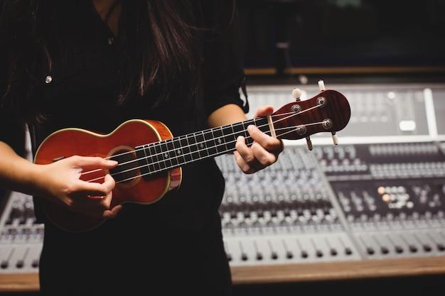 Kobieta w połowie sekcji gra na gitarze