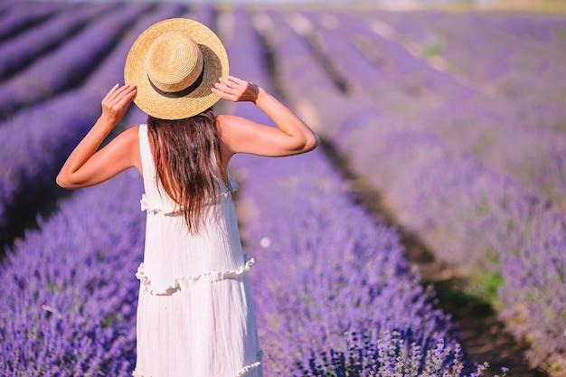 Kobieta w polu kwiatów lawendy o zachodzie słońca w białej sukni i kapeluszu