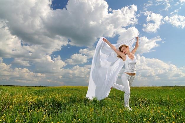 Kobieta w polu kwiatów z tkaniny jedwabne w dłoniach