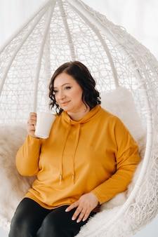Kobieta w pomarańczowej bluzie siedzi na niezwykłym krześle i pije kawę w domu.