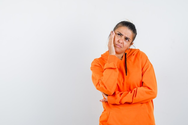 Kobieta w pomarańczowej bluzie z kapturem opierając się policzkiem na uniesionej dłoni i zamyślona