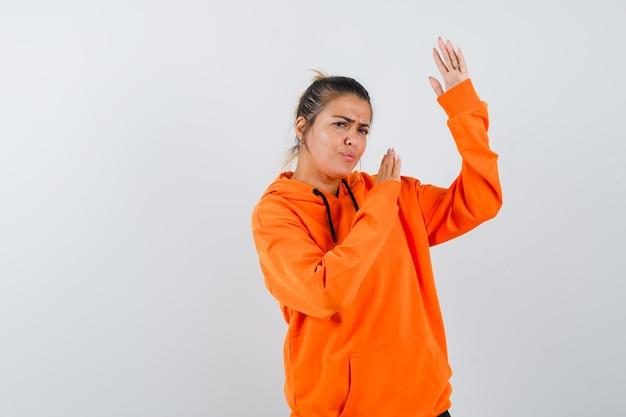Kobieta w pomarańczowej bluzie z kapturem pokazująca gest karate chop i wyglądająca na złośliwą