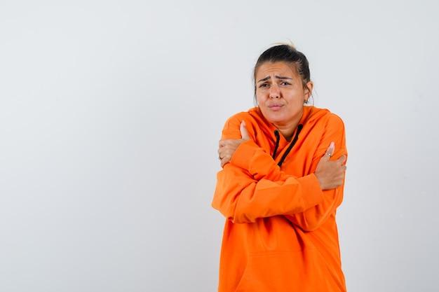Kobieta w pomarańczowej bluzie z kapturem przytula się lub czuje zimno i wygląda na bezradną