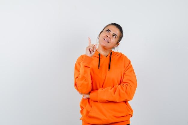 Kobieta w pomarańczowej bluzie z kapturem skierowana w górę i wyglądająca na marzycielską