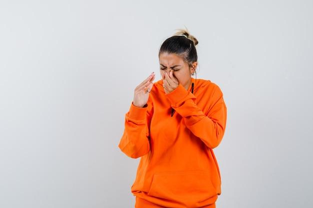 Kobieta w pomarańczowej bluzie z kapturem szczypie nos z powodu nieprzyjemnego zapachu i wygląda na zdegustowaną