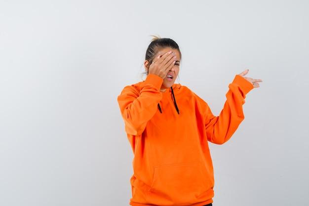 Kobieta w pomarańczowej bluzie z kapturem, wskazująca na bok, trzymająca rękę na oku i wyglądająca na przestraszoną