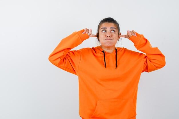 Kobieta w pomarańczowej bluzie z kapturem zatykająca uszy palcami i wyglądająca na ciekawą