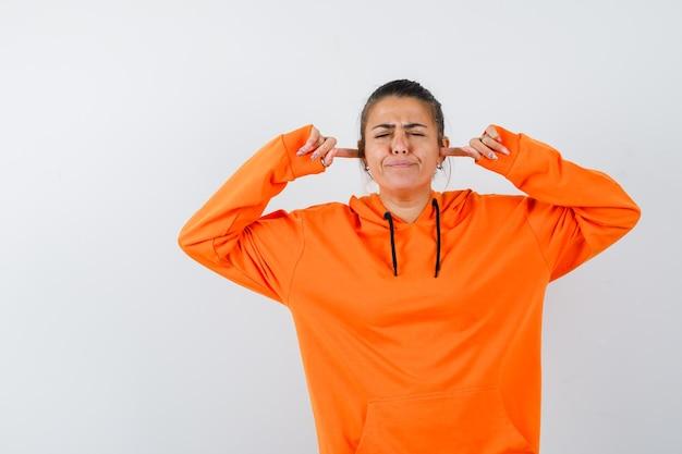 Kobieta w pomarańczowej bluzie z kapturem zatykająca uszy palcami i wyglądająca na zirytowaną