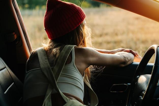 Kobieta w pomarańczowej czapce od zegarka chłodzi w samochodzie, ciesząc się widokami, opierając się o ramę okna. od tyłu.