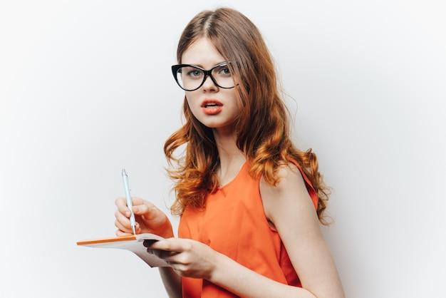 Kobieta w pomarańczowej koszuli z notatnikiem w ręce moda okulary.