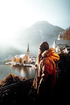 Kobieta w pomarańczowej kurtce stojącej na brązowym drewnianym doku w ciągu dnia