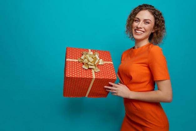 Kobieta w pomarańczowej sukience pozuje i utrzymuje duży prezent