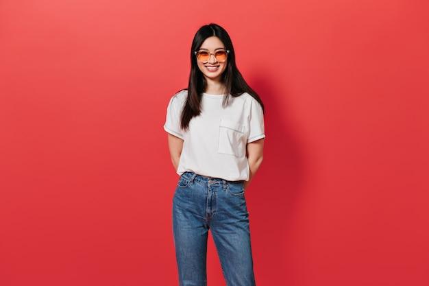 Kobieta w pomarańczowych okularach uśmiecha się na czerwonej ścianie