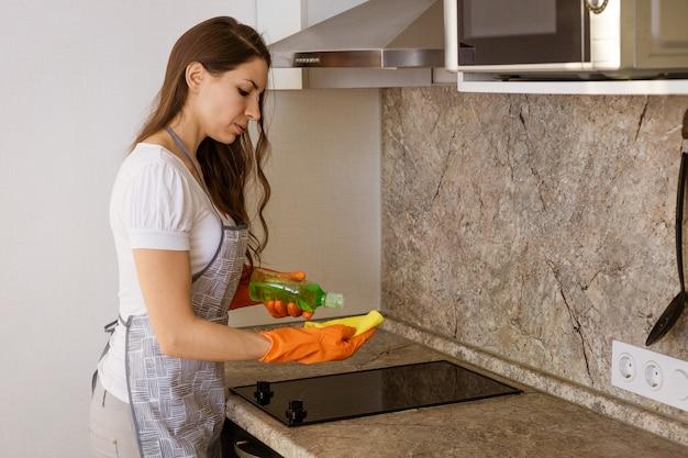 Kobieta w pomarańczowych rękawiczkach myje szmatą kuchenkę
