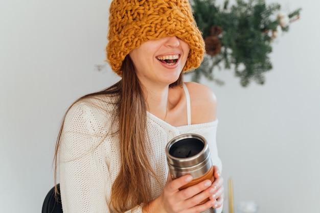 Kobieta w pomarańczowym kapeluszu i metalowym kubku termo wielokrotnego użytku na boże narodzenie zimowy dzień. zrównoważone życie