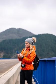 Kobieta w pomarańczowym płaszczu i wełnianym kapeluszu za pomocą telefonu komórkowego na drodze z górami