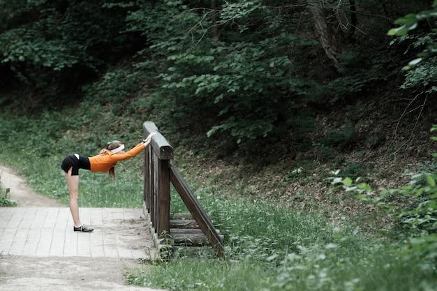 Kobieta w pomarańczowym sportowym kapturem rozgrzewa się przed joggingu