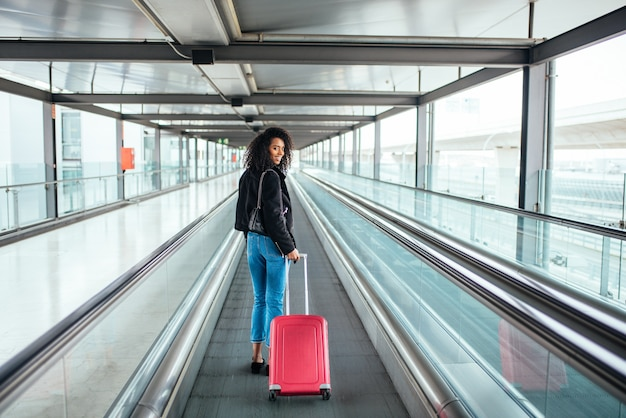 Kobieta w poruszającym się przejściu na lotnisku z różową walizką.