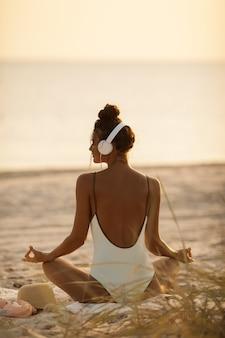 Kobieta w pozycji jogi medytacji ze słuchawkami na plaży