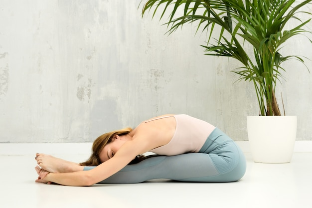 Kobieta w pozycji jogi w pozycji pascimottanasana lub w pozycji siedzącej do przodu w celu relaksu