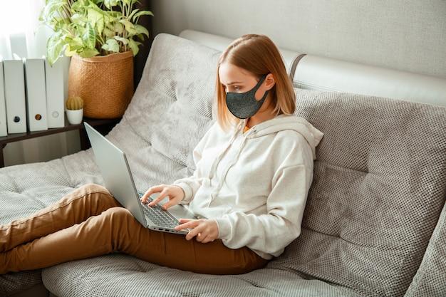 Kobieta w pracy maski ochronnej za pomocą laptopa w domowym biurze, siedząc na kanapie. nastoletnia dziewczyna w masce czy edukacja online za pośrednictwem laptopa covid 19 lockdown time. praca zdalna w pandemii koronawirusa.