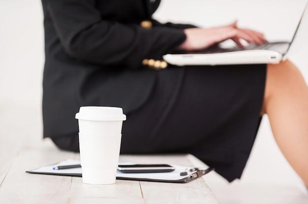 Kobieta w pracy. przycięty widok z boku bizneswoman siedzącej przy schodach i pracującej na laptopie