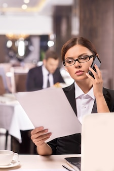 Kobieta w pracy. rozważna młoda kobieta w formalnym stroju rozmawia przez telefon i przegląda dokumenty siedząc w restauracji