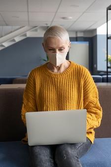 Kobieta w pracy ubrana w maskę medyczną
