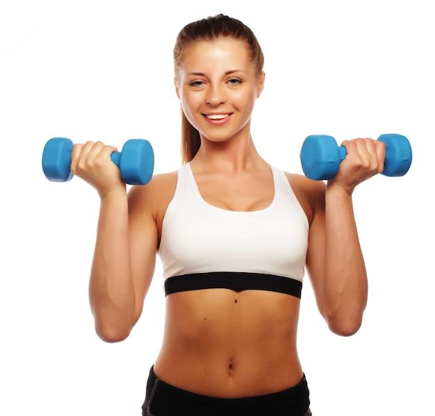 Kobieta w praktyce sprzętu sportowego z ciężarkami dłoni