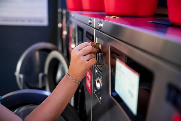 Kobieta w pralni. kobiecej ręki wkładając monetę do pralki.