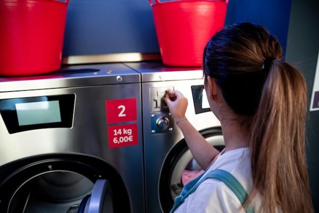 Kobieta w pralni. kobieta wkłada monetę do pralki.